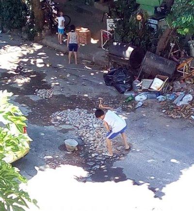 Un niño pica piedras para tapar bache