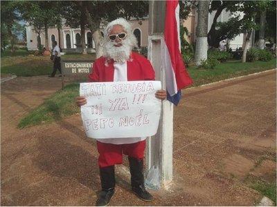 Vestido de Papá Noel, protesta frente a Municipio de Concepción