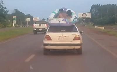 Graban a niños viajando en una piscina sobre el techo de un auto