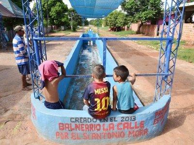 Zafan del calor y la falta de agua en una pileta callejera de Guarambaré