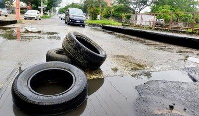 Vecinos usan neumáticos para señalizar cráteres