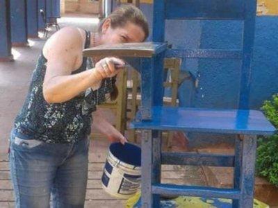 Directora ayuda a padres a pintar  sillas en escuela pública de Luque