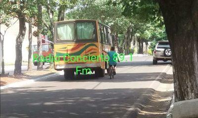 Adolescente en bicicleta se sostiene por la puerta de un colectivo en marcha