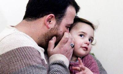 Hombre enseña a su hija a reírse de los bombardeos