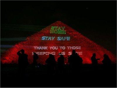 """La gran pirámide de Guiza, iluminada con la frase """"Quedate en casa"""""""